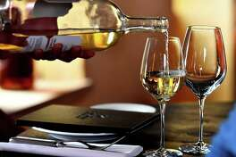 An person poors Sauternes wine on a glass on May 14, 2018 in Sauternes, western France. A sweet wine that is savoured with foie gras at Christmas: it is this old-fashioned image that Sauternes wants to break by seducing a younger clientèle through wine tourism. This vineyard south of Bordeaux wants to regain its aura of yesteryear, when, during the prestigious ranking of the grands crus of 1855, the prices of the 27 castles Sauternes and Barsac exceeded those of Bordeaux reds. / AFP PHOTO / GEORGES GOBETGEORGES GOBET/AFP/Getty Images