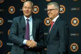 Houston Astros owner Jim Crane, left, shakes hands with Jeff Luhnow after promoting him to president of baseball operations and general manager during a news conference at Minute Maid Park on Monday, June 18, 2018, in Houston.
