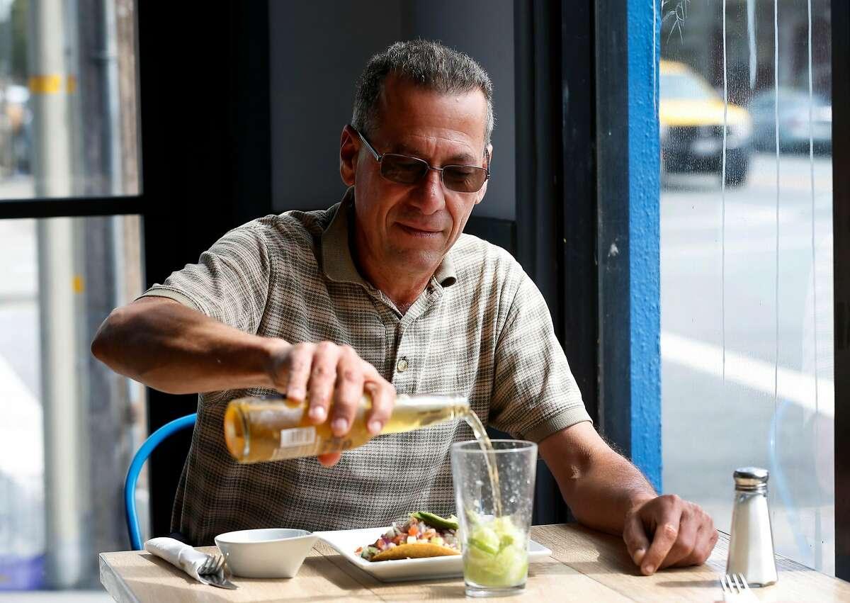 Ricardo Herrera has a beer with his shrimp tostada at Rincon Nayarit.