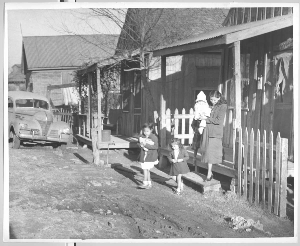 January 1950: A family in Schrimpf Alley, a neighborhood outside of downtown, near Navigation and Jensen Drive.