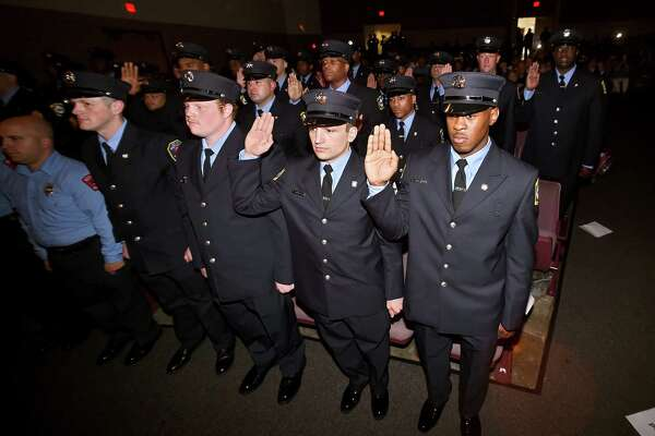 Recruits from the New Haven Regional Fire Training Academy recite the oath of office with New Haven Mayor Toni Harp during the 61st Recruit Class Graduation at Career High School in New Haven on June 18, 2018.