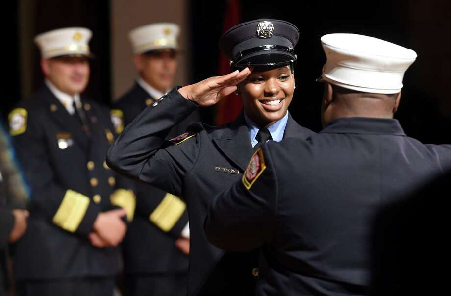 Shytanya Floyd salutes New Haven Fire Department Chief John Alston, Jr., as she gets her badge during the New Haven Regional Fire Training Academy's 61st Recruit Class Graduation at Career High School in New Haven on June 18, 2018. Photo: Arnold Gold, Hearst Connecticut Media / New Haven Register
