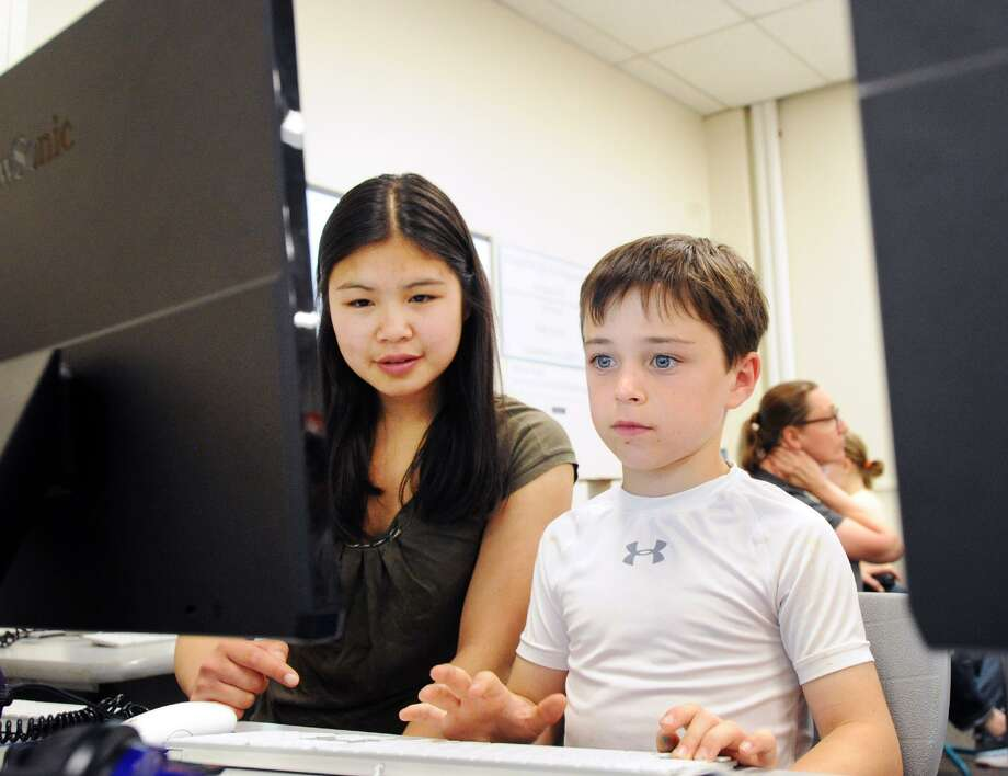 Greewich High School senior Michelle Woo, 17, left, teaches computer coding to Riverside School second grade student Adler Weinberg, 7, at the Riverside School in Greenwich, Conn., Tuesday, June 12, 2018. Photo: Bob Luckey Jr. / Hearst Connecticut Media / Greenwich Time