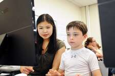Greewich High School senior Michelle Woo, 17, left, teaches computer coding to Riverside School second grade student Adler Weinberg, 7, at the Riverside School in Greenwich, Conn., Tuesday, June 12, 2018.