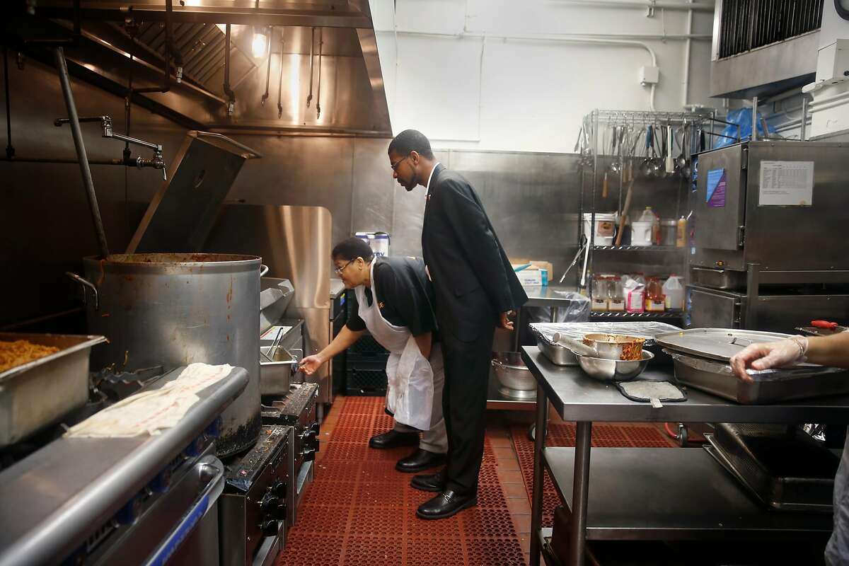 Joann Adams (l to r), cook, shows Reverend Theon L. Johnson III, associate professor Glide Memorial United Methodist Church, the new tilting skillet in the kitchen while she works in the kitchen during the dinner meal service at Glide Memorial on Thursday, July 9, 2015 in San Francisco, Calif.