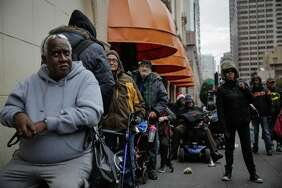 Laurence Heard (left) and other guests wait outside Glide for a free Christmas Eve lunch hosted by the House of Prime Rib.