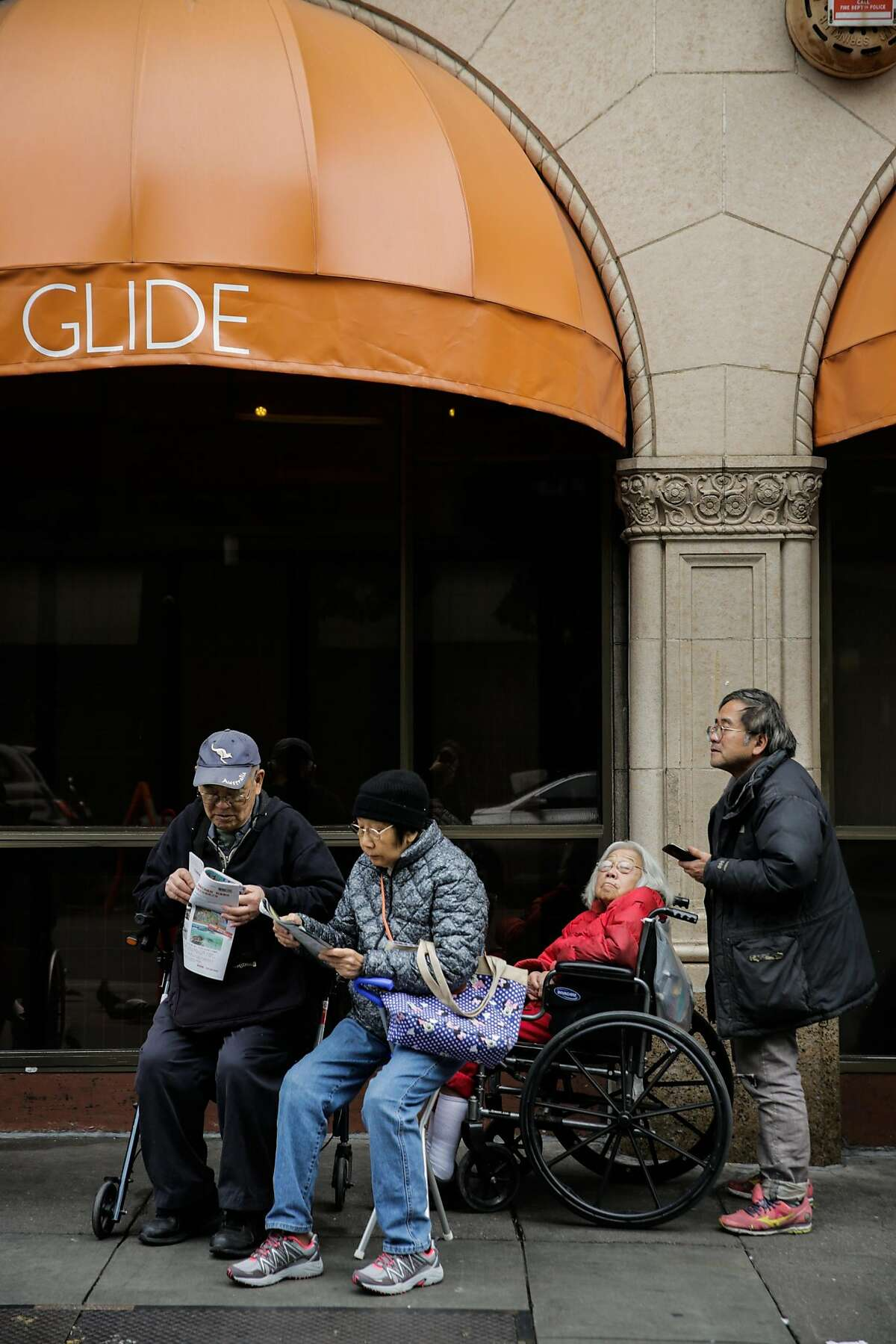 People wait outside Glide Memorial Church ahead of a free Christmas Eve lunch hosted by House of Prime Rib in San Francisco, Calif., on Sunday, Dec. 24, 2017.