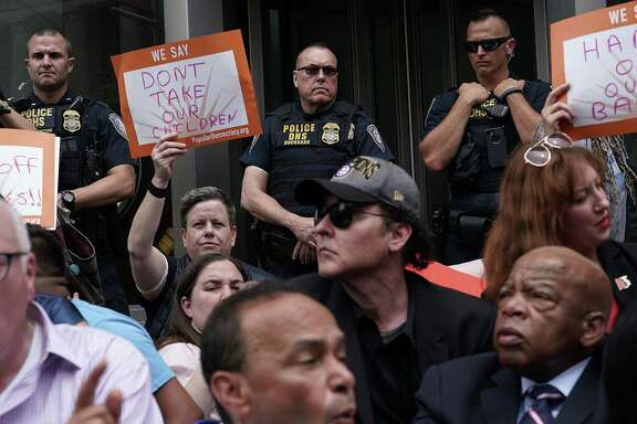 Department of Homeland Security police officers watch demonstrators outside the headquarters of U.S. Customs and Border Protection during a protest Wednesday in Washington, DC. A reader says object of the new policy isn't cruel.