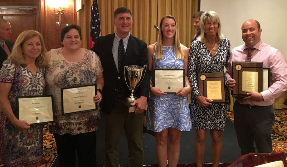 Greenwich High School received the FCIAC Cup for having the top athletic program for 2017-2018. Athletic director Gus Lindine, center, holds the cup-shaped trophy and is joined by from left to right, Sue Knight (gymnastics coach), Ally Orrico (field hockey coach), Kaitlin Gaghan (girls lacrosse coach), Betsy Underhill (girls tennis) and Evan Dubin (girls track and field, cross country). Photo: Contributed Photo / Contributed Photo / Stamford Advocate Contributed