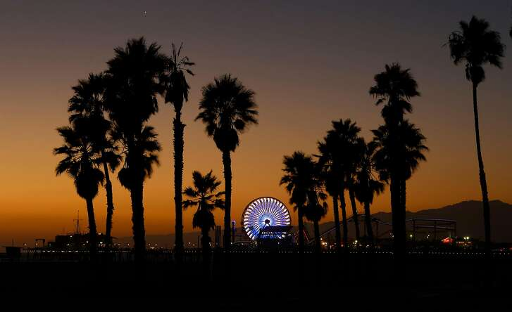 FILE - In this Oct. 11, 2013 file photo, the Ferris wheel at Pacific Park on the Santa Monica Pier is illuminated in Santa Monica, Calif. The relocation of tech companies to southern California is part of a growing movement of U.S. cities seeking to duplicate the formula that turned northern California�s Silicon Valley, slightly south of San Francisco, into a mecca of society-shifting innovation and immense wealth. (AP Photo/Mark J. Terrill, File)