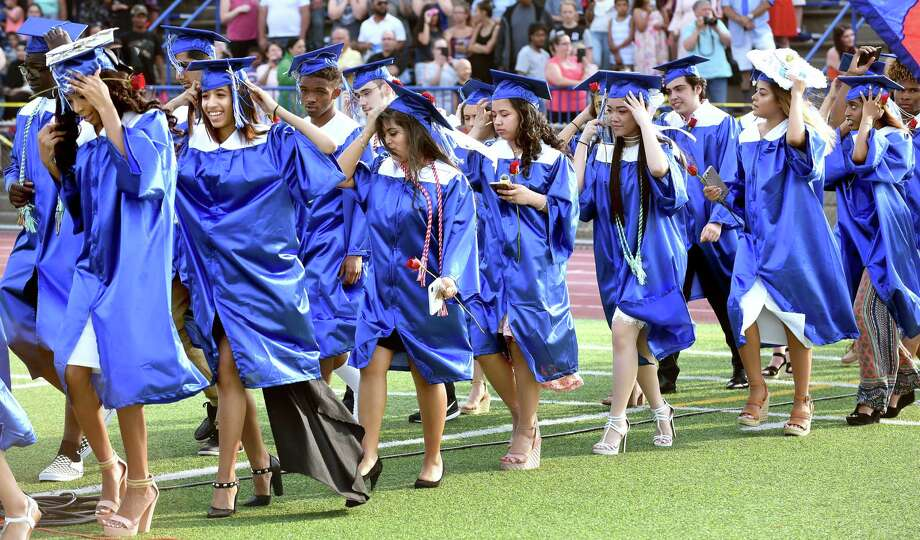 Graduates hold onto their caps as a gust of wind passes as they enter the football field for graduation at West Haven High School on June 18, 2018. Photo: Arnold Gold, Hearst Connecticut Media / New Haven Register
