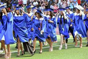 Graduates hold onto their caps as a gust of wind passes as they enter the football field for graduation at West Haven High School on June 18, 2018.