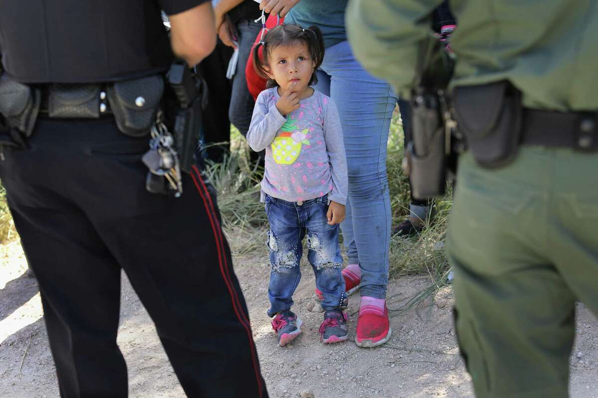 MCALLEN, TX - JUNE 12: A Mission Police Dept. officer (L), and a U.S. Border Patrol agent watch over a group of Central American asylum seekers before taking them into custody on June 12, 2018 near McAllen, Texas. Local police officers often coordinate with Border Patrol agents in the apprehension of undocumented immigrants near the border. The immigrant families were then sent to a U.S. Customs and Border Protection (CBP) processing center for possible separation. U.S. border authorities are executing the Trump administration's