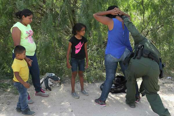 """MCALLEN, TX - JUNE 12:  Central American asylum seekers are taken into custody by U.S. Border Patrol agents on June 12, 2018 near McAllen, Texas. The families were then sent to a U.S. Customs and Border Protection (CBP) processing center for possible separation. U.S. border authorities are executing the Trump administration's """"zero tolerance"""" policy towards undocumented immigrants. U.S. Attorney General Jeff Sessions also said that domestic and gang violence in immigrants' country of origin would no longer qualify them for political asylum status.  (Photo by John Moore/Getty Images)"""