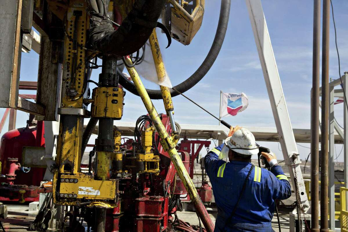A roughneck cleans the drilling floor of a rig drilling for Chevron in the Permian Basin near Midland, Texas. CONTINUE to see scenes from the 2018 Permian Basin International Oil Show.