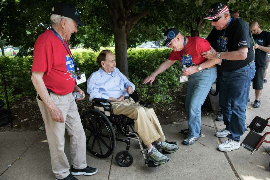 Navy veteran Leon Brooks of Nevada, second from right, got out of his wheelchair to greet former Senator Bob Dole, R-Kansas, while Air Force veteran James Howerton, far left, watches, at the National World War II Memorial during an Honor Flight trip to Washington, D.C., on June 9, 2018. Photo: Photo For The Washington Post By Cheryl Diaz Meyer / Copyright 2018 Cheryl Diaz Meyer. All Rights Reserved.