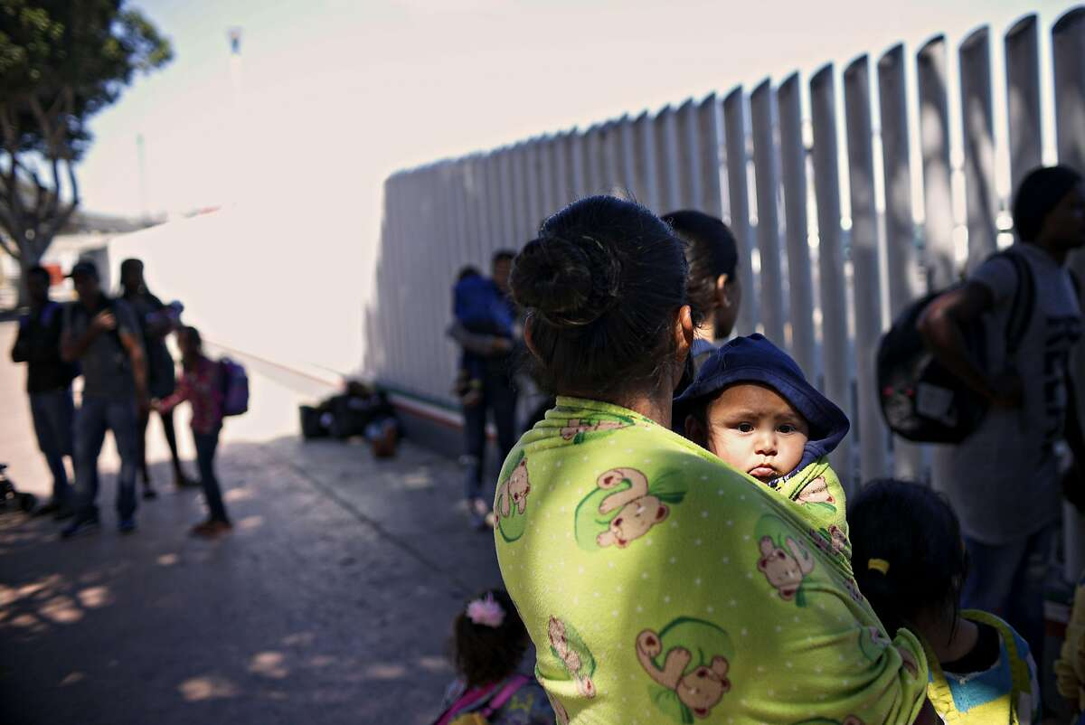 TIJUANA, MEXICO - JUNE 18: Undocumented migrants wait for asylum hearings outside of the port of entry in Tijuana, Mexico on Monday, June 18, 2018. The Trump administration will no longer accept victims of domestic abuse or gang violence seeking asylum. (Photo by Sandy Huffaker/Getty Images)