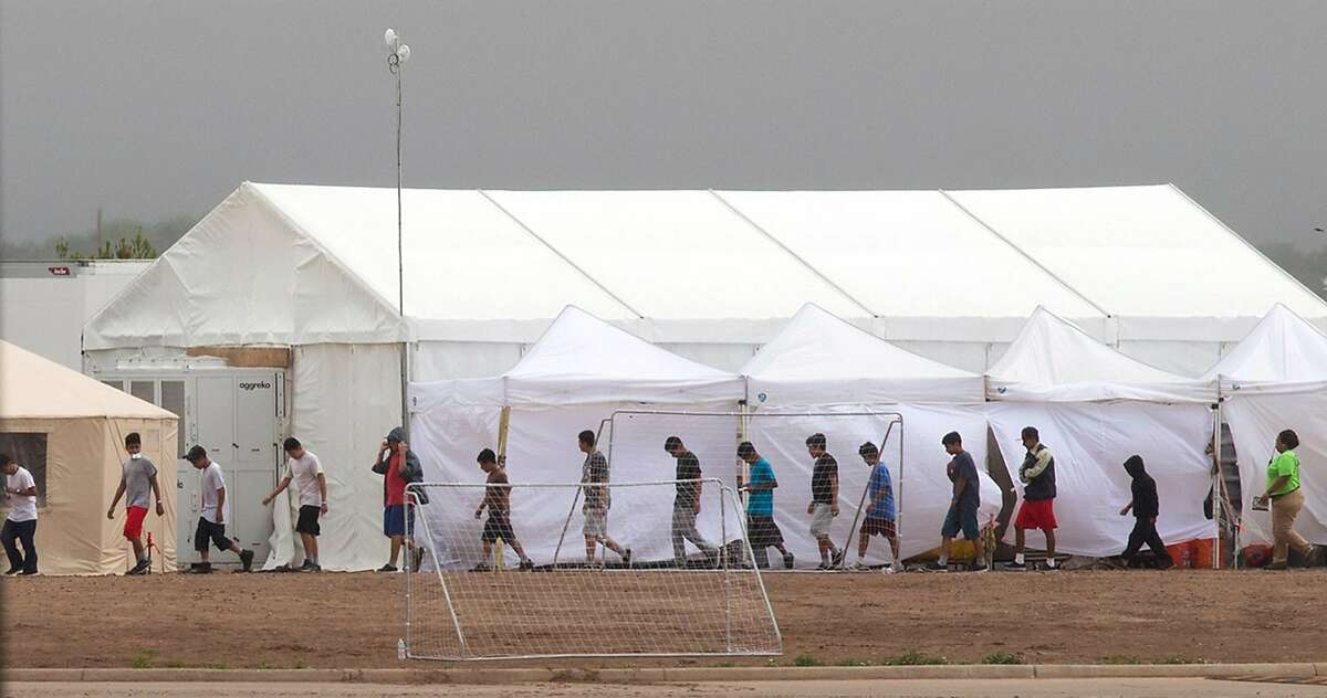 """Immigrant kids walk through the C.B.P. facility where the newly formed """"tent city"""" is located, Saturday, June 16, 2018, in Tornillo. Photo by Ivan Pierre Aguirre/ for the San Antonio Express-News"""