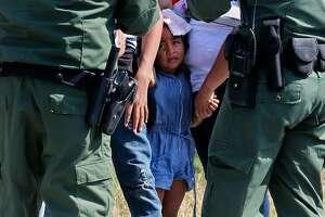 U.S. Border Patrol agents question adult and child immigrants near Anzalduas Park, southwest of McAllen, Texas.