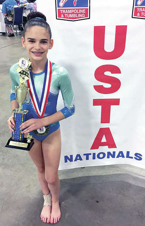 Mid Illinois gymnast/tumbler Allison Wooden with the trophy she was awarded following a tie for third place overall in the top ten trophy round of Intermediate division at the US Tumbling and Trampoline Championships Saturday in Fort Lauderdale, Florida