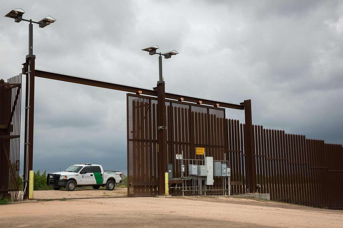 A US Border Patrol agent keeps watch at a gate on the US-Mexico border fence on June 18, 2018 near San Benito, Texas.