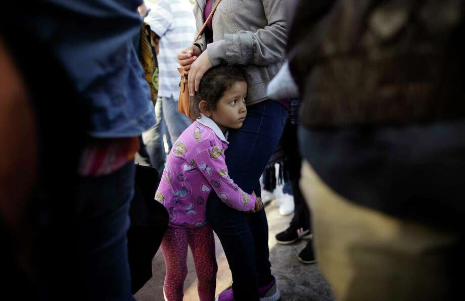 In this June 13, 2018 photo, Nicole Hernandez, of the Mexican state of Guerrero, holds on to her mother as they wait with other families to request political asylum in the United States, across the border in Tijuana, Mexico. The family has waited for about a week in this Mexican border city, hoping for a chance to escape widespread violence in their home state. (AP Photo/Gregory Bull) Photo: Gregory Bull / Copyright 2018 The Associated Press. All rights reserved.