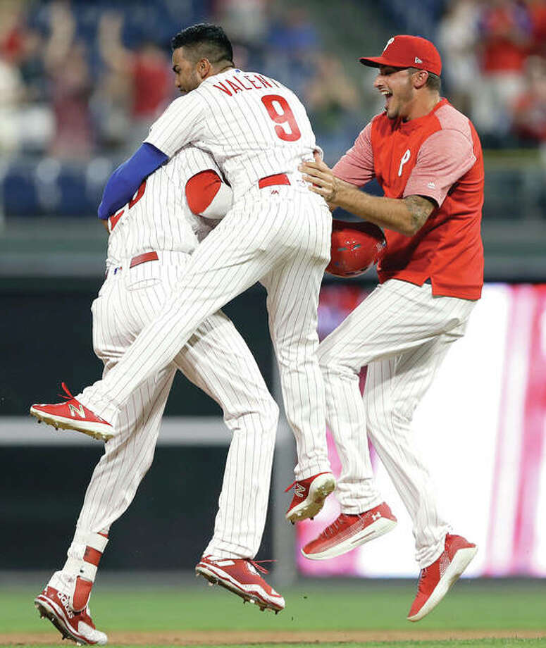 The Phillies' Aaron Altherr, left, celebrates with teammates after hitting a game-winning two-run double off Cardinals relief pitcher Matt Bowman in the 10th inning Monday night in Philadelphia. The Phillies won 6-5. Photo:       Matt Slocum | AP Photo