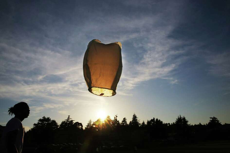 Friends and family of Charleena Lyles, including Stanley Parker III, left, release paper lanterns during a remembrance event on the one-year anniversary of her death, Tuesday, June 18, 2018 at Magnuson Park.  Lyles was killed one year ago by Seattle Police officers in her apartment after she called them for assistance.