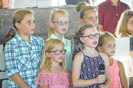 """A group of young Greene County 4-H members kick off the day's festivities with an impromptu singing of the """"Star Spangled Banner"""" at the Greene County Fair on Monday."""