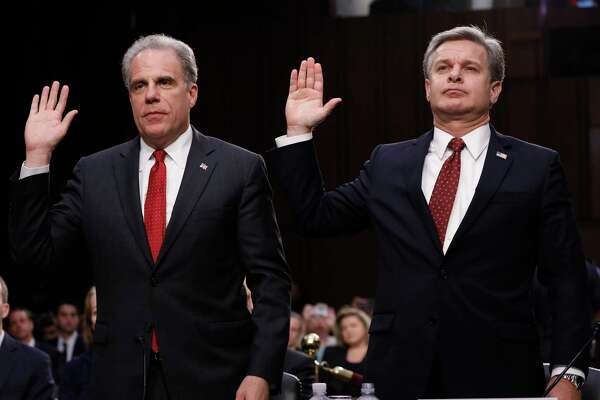 Michael Horowitz, inspector general with the Department of Justice, left, and Christopher Wray, director of the Federal Bureau of Investigation, swear in to a Senate Judiciary Committee hearing on Monday.