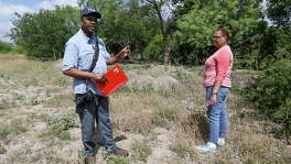 Local historian Everett Fly (left) and Melanie Winters Brooks look over the site of the Winters-Jackson cemetery, an African American graveyard on the northeast side that dates back to the late 1800s, on Thursday, May 31, 2018.  In 1986, without consent, land developers removed the remains of 72 people from the private cemetery and reinterred them at nearby Holy Cross Cemetery.  MARVIN PFEIFFER/mpfeiffer@express-news.net