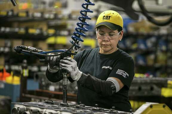 Margarita Cardenas attaches an engine head at Caterpillar's Seguin engine manufacturing plant June 13, 2018. The plant exports 70 percent of its engines.