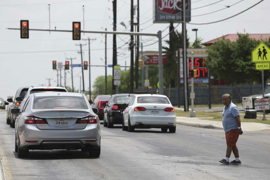 A pedestrian looks for oncoming traffic while crossing Culebra Road west of the intersection with NW 24th Street, June 10. Despite safety measures and hard-to-explain statistical spikes, pedestrian-auto deaths in San Antonio are still troubling. Photo: JERRY LARA /San Antonio Express-News / San Antonio Express-News