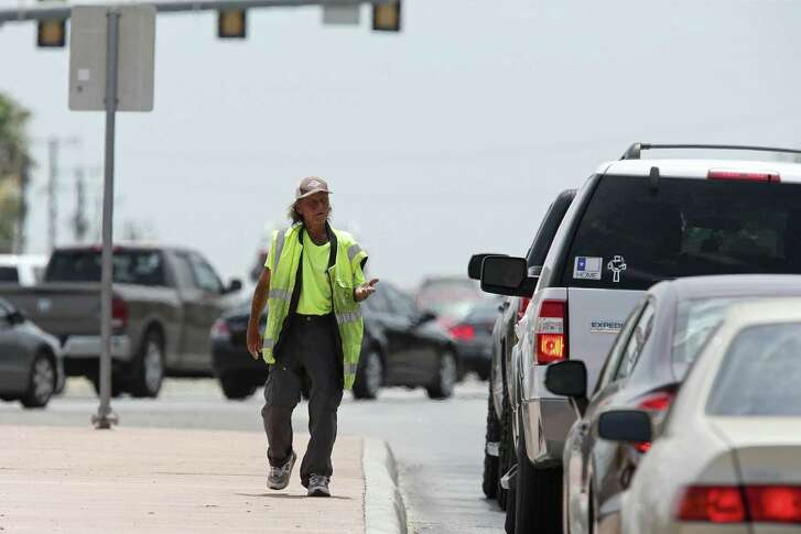 A panhandler works the traffic  at a stoplight on Culebra Road west of the intersection with NW 24th Street, Sunday, June 10, 2018. Despite safety measures and hard-to-explain statistical spikes, pedestrian-auto deaths in San Antonio are still troubling. Dozens of people, 50 or 60 some years, die due to being drunk or on drugs, wearing dark clothing at night or because they couldn't navigate one of SA's notorious 7-lane mega roads, such as San Pedro, Blanco, Military, Fredericksburg and, perhaps the worst, Culebra.