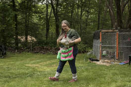 Crystal Cahill leaves a chicken coop behind her home in Great Meadows, N.J., with a rooster in her arms.