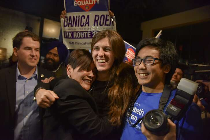 Danica Roem, center, who ran for house of delegates against GOP incumbent Robert Marshall, is greeted by supporters as she prepares to give her victory speech with Prince William County Democratic Committee at Water's End Brewery on Tuesday, Nov. 7, 2017, in Manassas, Va. Roem will be the first openly transgender person elected and seated in a state legislature in the United States. (Jahi Chikwendiu/The Washington Post via AP)