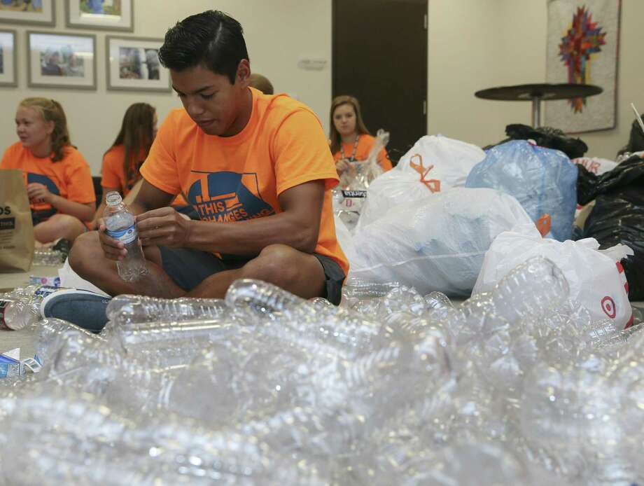 Living Word Lutheran Church High School Youth Group memer Ismael Castillo peels a label off of a plastic water bottle for an art installation project for a part of the upcoming Evangelical Lutheran Church in America's (ELCA) ELCA Youth Gathering on Friday, June 15, 2018, in Katy. The church collected over 2,000 plastic bottles from a drive in the span of roughly a month. More than 30,000 youth, adult leaders and others from the ELCA from all over the nation will participate in the ELCA Youth Gathering in Houston June 25-July 1. ( Yi-Chin Lee / Houston Chronicle ) Photo: Yi-Chin Lee / Houston Chronicle / © 2018 Houston Chronicle