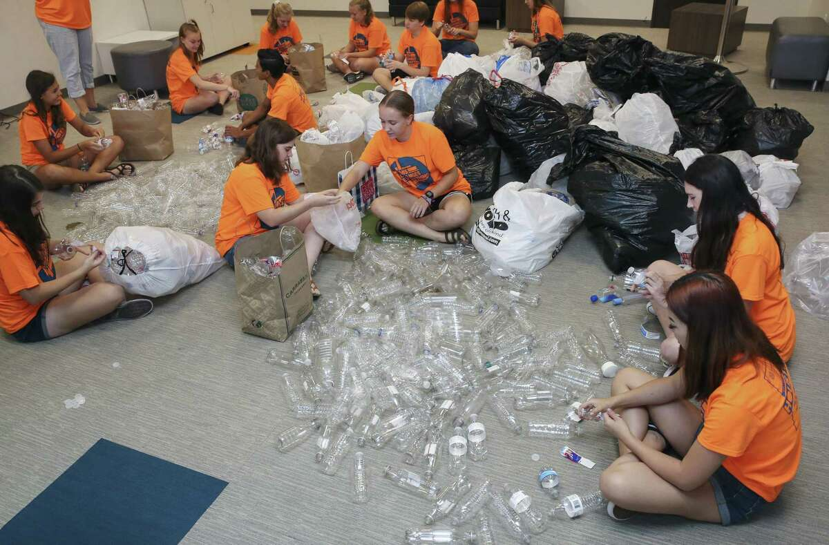 Living Word Lutheran Church High School Youth Group memers peel off labels and take off caps of plastic water bottles for an art installation project for a part of the upcoming Evangelical Lutheran Church in America's (ELCA) ELCA Youth Gathering on Friday, June 15, 2018, in Katy. The church collected over 2,000 plastic bottles from a drive in the span of roughly a month. More than 30,000 youth, adult leaders and others from the ELCA from all over the nation will participate in the ELCA Youth Gathering in Houston June 25-July 1. ( Yi-Chin Lee / Houston Chronicle )