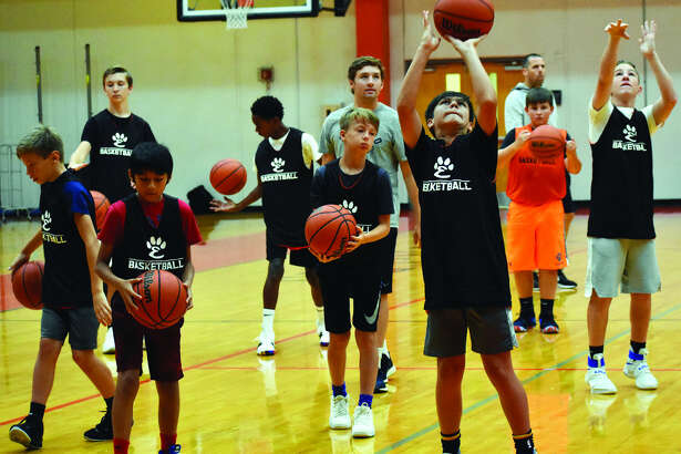 Participants of the Edwardsville boys' basketball camp practice shooting forms during Tuesday's session inside the District 7 Sports Complex.