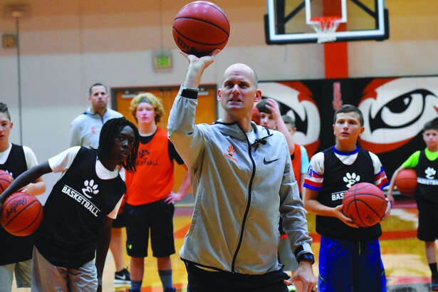 Edwardsville boys' basketball coach Dustin Battas teaches shooting form during a drill inside Lucco-Jackson Gymnasium.