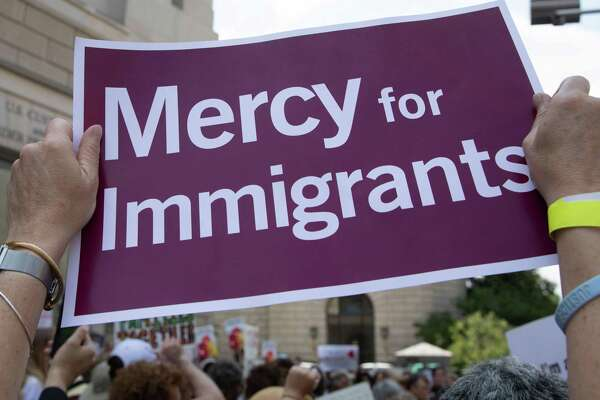 A demonstrator holds a protest sign during a rally against the separation of immigrant minors and their parents outside the Customers and Border Protection headquarters in Washington. Online donors have responded to call to assist immigrants separated from children in effort that helps S.A.-based legal nonprofit group RAICES.