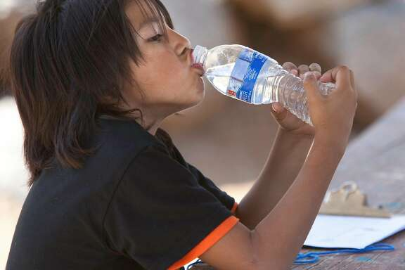 Porterville, CA--- Rozen Santos,6, enjoys a bottle of water during a field day at  Citrus South Tule School. Students competed in different activities that emphasized exercise and the spirit of competition with an Olympic theme. Students drink bottled water at the school because the groundwater basin under the school is loaded with nitrates.