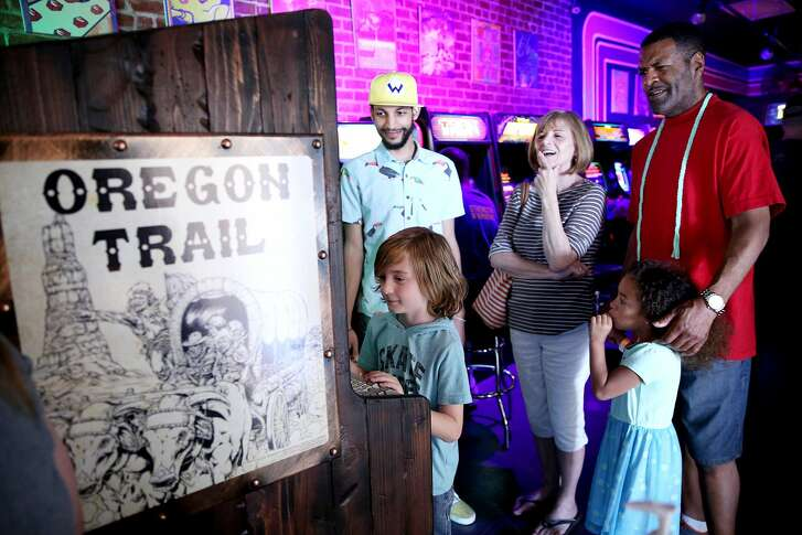 From left: Sebastian Gross, 7, plays the Oregon Trail game as Jonathan Williams, Joanne Gross, Annleah Moore, 6, and Robert Moore watch and wait for a turn at High Scores Arcade, Saturday, June 16, 2018, in Hayward, Calif.