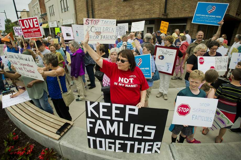 More than 100 people gather to protest the Trump administration's decision to separate immigrant families at the border on Tuesday, June 19, 2018 in downtown Midland. After speakers addressed the crowd at the corner of Main and McDonald, the crowd marched down Main Street to the Midland County Courthouse, where a rededication ceremony was underway for the courthouse's new entryway. (Katy Kildee/kkildee@mdn.net) Photo: (Katy Kildee/kkildee@mdn.net)