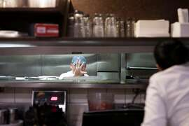 FILE-- A cook waves toward a server at a restaurant in New York, Nov. 19, 2017. The Trump administration announced a sweeping new rule on June 19, 2018, that will make it easier for small businesses to band together and set up health insurance plans that skirt many requirements of the Affordable Care Act, offering lower costs but also fewer benefits. Officials said the new association health plans might appeal to restaurant workers. (Dan Balilty/The New York Times)
