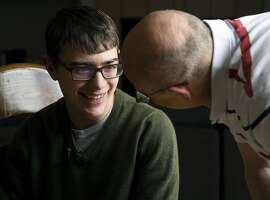 In this Monday, April 23, 2018, photo, Lukas Inman, 19, interacts with his father in Colorado Springs, Colo. Inman suffers from a rare and severe form of epilepsy called Lennox-Gastaut Syndrome. A British pharmaceutical company is getting closer to a decision on whether the U.S government will approve the first prescription drug derived from the marijuana plant, but parents, including Lukas,' who for years have used cannabis to treat severe forms of epilepsy in their children are feeling more cautious than celebratory. (AP Photo/Thomas Peipert)