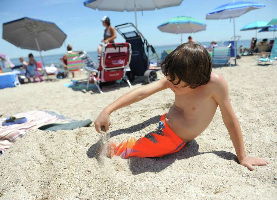 Braden Danow, 9, of Rye Brook, N.Y., buries himself in the sand on the beach at Greenwich Point Park Sunday. With Sunday's temperature nearing 90 degrees, the beach saw a lot of activity from locals and out-of-towners alike. Photo: Tyler Sizemore / Hearst Connecticut Media / Greenwich Time