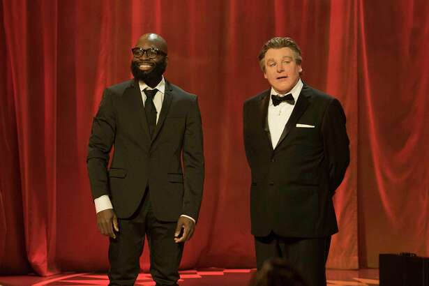 "Obaroene Otitigbe, left, an art teacher in Albany public schools, talks with ""Gong Show"" host Mike Myers, in the character of a British comedian named Tommy Maitland, about Otitigbe's aerial hooping act on the premiere of the second season of ""The Gong Show"" on Thursday night on ABC."