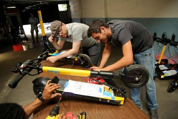 Nate Booth (left), German Gladkov (right) and Justin Jenkins (bottom) maintain the scooters at Skip, Friday, June 15, 2018, in San Francisco, Calif. Skip, a scooter rental, is one of 12 companies applying for a permit to have an e-scooter program in the city.