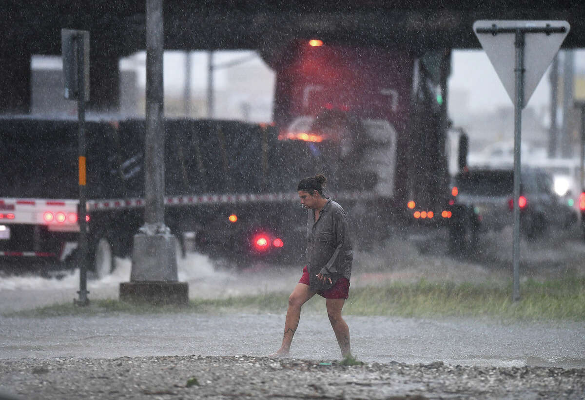A woman crosses Twin City Highway near Texas 73 during Tuesday's rain. Several streets in southern Jefferson County were closed to prevent water from being pushed into homes. Photo taken Tuesday, 6/19/18